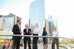 Happy business team members talking outside in  . Satisfied business team members speaking outdoors in  . Concept of biz partners enjoying successful result Stock Photo