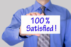 100 satisfied. Businessman in blue shirt and gray tie shows a card with the inscription 100 satisfied. Man on a gray background. Selective focus Stock Images