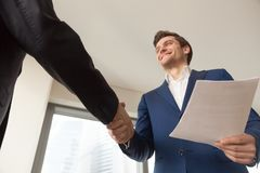Smiling company manager welcoming client in office. Satisfied businessman with business documents shaking hand to partner, making deal after reviewing terms of stock photography