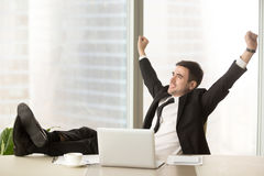 Satisfied businessman happy to finish work with laptop, celebrat. Satisfied businessman happy to finish work with laptop at office, raises hands and puts feet up Stock Photo