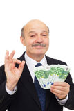Satisfied businessman loves money and sniffing them with admirat Stock Photos