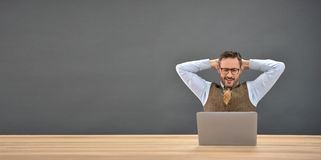 Satisfied businessman relaxing in front of laptop Stock Images