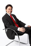 Satisfied businessman sitting in a chair Royalty Free Stock Image