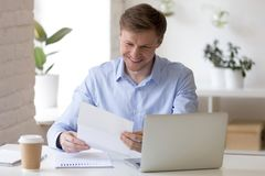 Satisfied businessman sitting at the desk reading letter royalty free stock photos