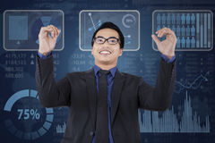 Satisfied businessperson achieve his vision. Young businessman expressing satisfied in front of modern business chart background Stock Images