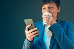 Satisfied businesswoman drinking coffee to go and looking mobile Royalty Free Stock Photography