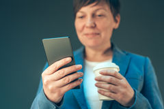 Satisfied businesswoman drinking coffee to go and looking mobile Royalty Free Stock Photo