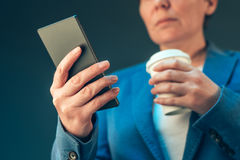 Satisfied businesswoman drinking coffee to go and looking mobile Stock Images