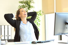 Satisfied businesswoman relaxing at office. Satisfied businesswoman with arms on the head laughing sitting on a chair and relaxing at office Stock Photos
