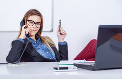 Satisfied businesswoman talking over the phone. Satisfied businesswoman in her office talking over the phone Stock Photos