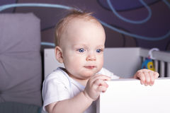 Satisfied and calm baby boy in his bed. An infant kid staying in a crib Royalty Free Stock Photo