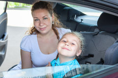 Satisfied Caucasian mother and little child fastened in safety car seat Royalty Free Stock Photography