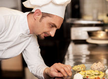 Satisfied chef analyzing dish before serving Royalty Free Stock Images