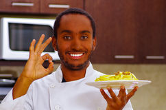 Satisfied chef wearing white clothes making circle with fingers expressing exquisite taste, smiling happily holding Royalty Free Stock Photos