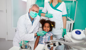 Satisfied child with dentist after treatment. Satisfied black child with dentist after treatment Royalty Free Stock Photos