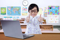 Satisfied child giving thumbs up in classroom Royalty Free Stock Image