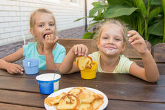 Satisfied children at a table in courtyard eating pancakes with sour cream Royalty Free Stock Photos