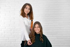 Satisfied client smiling in beaty studio with hairstylist standing behind. royalty free stock images