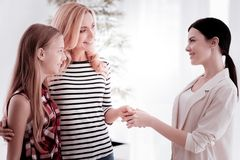 Satisfied clients shaking hands with their psychoanalyst and smiling. Grateful clients. Cheerful kind young women hugging her pretty teenage daughter while stock image