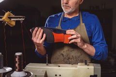 Satisfied cobbler looking at footwear. Artisan in apron enjoys his work with a shoe stock image