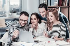 Satisfied confident employees focusing on the laptop and making notices. Stock Image