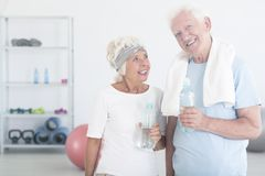 Satisfied couple of elderly people. In sportswear drinking water after stretching exercises in fitness center Royalty Free Stock Image