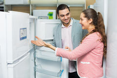 Satisfied  couple looking at large fridges Royalty Free Stock Images