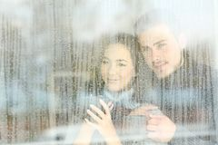 Satisfied couple looking through a window at home Stock Photos