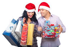 Satisfied couple of  their purchasing things. Happy couple at shopping for Christmas  looking in bags and  being satisfied of what they bought isolated on white Royalty Free Stock Photo