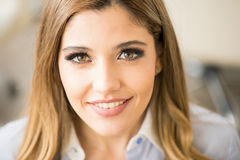 Satisfied customer in a beauty salon. Gorgeous young woman looking happy and satisfied after her getting her makeup done in a beauty salon stock image