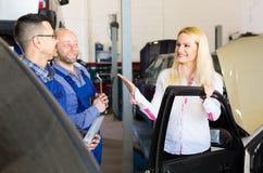 Satisfied customer at car repair shop Royalty Free Stock Images
