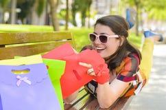 Satisfied Customer Enjoying Shopping. Smiling woman lying on bench in park enjoying shopping royalty free stock images