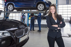 Satisfied customer in garage. Happy customer in garage with her repaired car in the background stock photos