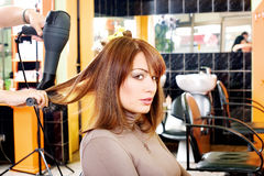 Satisfied customer in a hair salon. A satisfied female customer in a hair salon stock image