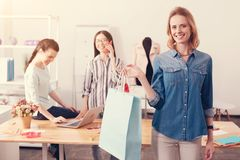 Satisfied customer holding a bag with clothes. Best purchase. Satisfied beautiful customer holding a bag with clothes in right hand and smiling while tailors royalty free stock photos