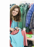 Satisfied customer holding clothes in supermarket. Happy woman showing some clothes in supermarket out of the cloakroom stock photo