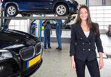Satisfied customer standing in front of her car at a garage royalty free stock image