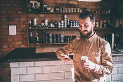 Satisfied customer is stanfing and holding a phone and looking at it. Also he has a cup in his hands. Guy looks cheerful. And satisfied royalty free stock photography