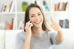 Satisfied customer talking on phone and looking at you. Sitting on a sofa at home Stock Photo