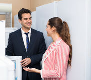 Satisfied customers looking at large fridges Royalty Free Stock Images