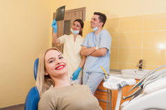 Satisfied dental team and female patient Stock Photo