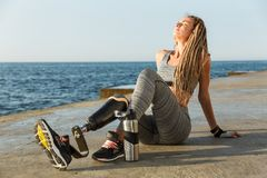 Satisfied disabled athlete woman with prosthetic leg. Sitting at the beach with water bottle stock photo