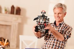 Satisfied engineer examining his new robotic creation. I think its perfect. Selective focus on an impressive robotic machine held by a senior engineer smiling Royalty Free Stock Photography