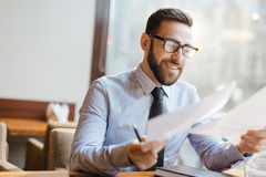 Satisfied entrepreneur in cafe. Portrait of confident bearded entrepreneur sitting at table in restaurant, holding business papers and smiling happily after Stock Image