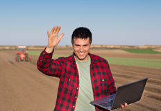 Satisfied farmer with laptop and tractor Royalty Free Stock Photo