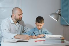 Father and son work together on school homework or homeschooling. stock image