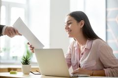 Satisfied female intern getting positive feedback from employer. Satisfied female company intern happy to see good work results, receiving document report from stock images