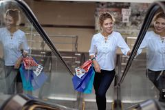 Satisfied female customer driving up on escalator in mall. Satisfied female customer driving up on escalator, smiling and looking at shops in mall. Pretty curly stock images