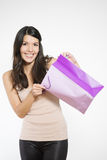 Satisfied female customer with her purchase. Satisfied beautiful young female customer with her purchase held in a purple recyclable paper shopping bag smiling royalty free stock images