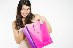Satisfied female customer with her purchase. Satisfied beautiful young female customer with her purchase held in a purple recyclable paper shopping bag smiling royalty free stock photo